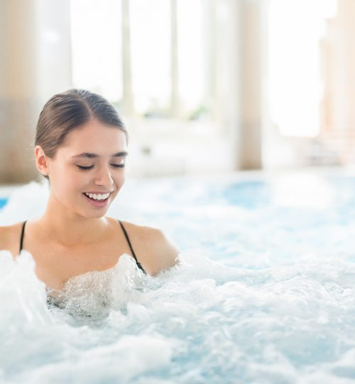 Young woman enjoying warm gentle water waves in whirlpool